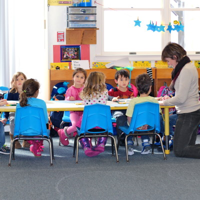 A small group assembles at the table to complete a project that reinforces a learning theme.
